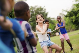 In the focus of the shot, children of various races are seen pulling a rope, presumably playing a game of tug-of-war.